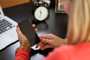 woman checking phone in home office